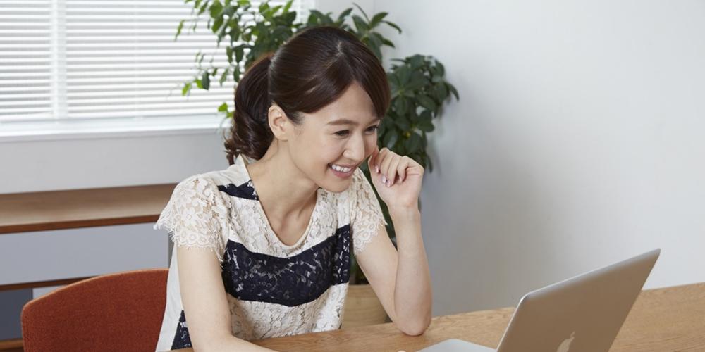 笑顔でパソコンをする女性